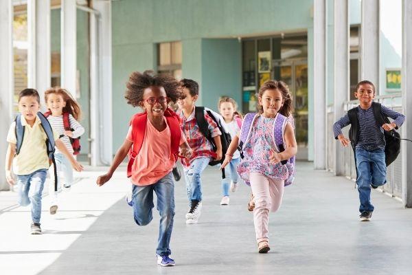 Children with backpacks running through school corridor